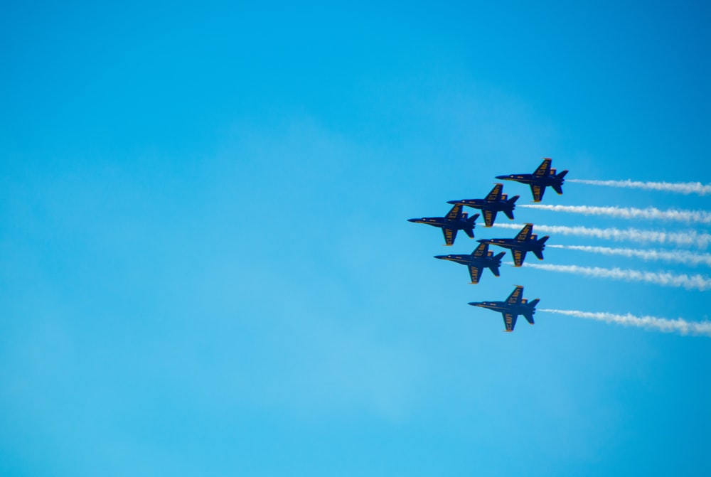 six black fighter jets doing air show during daytime