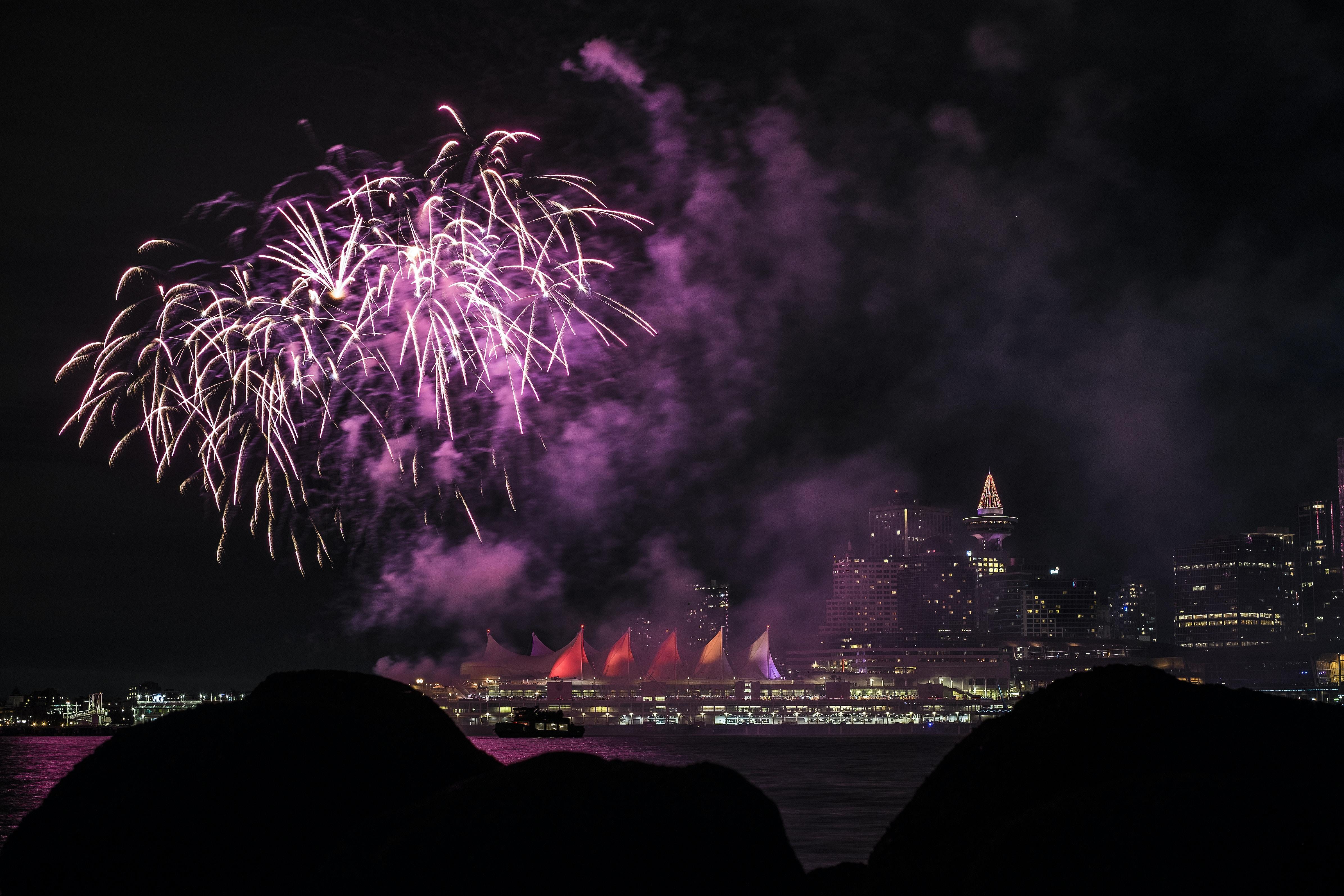 fireworks above city skyline at night-time