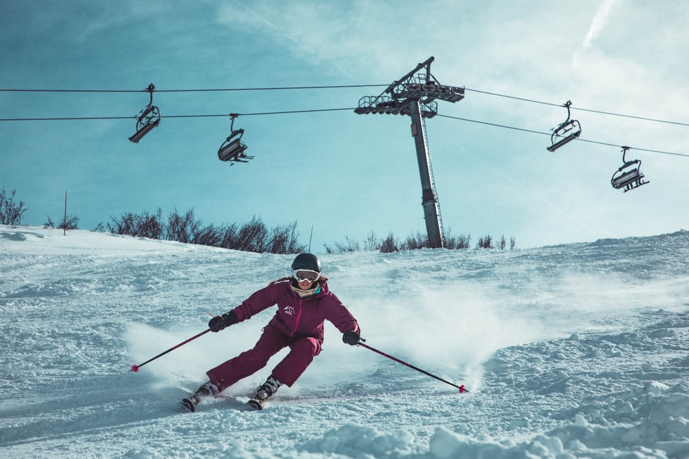 person doing snow ski under cable cars