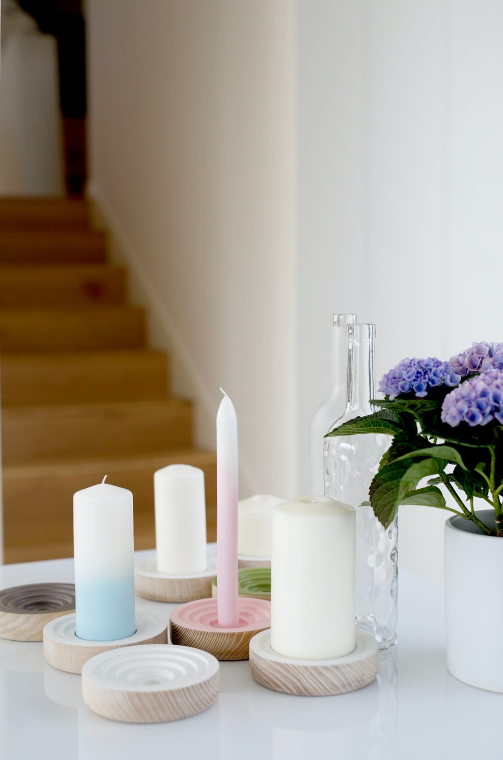 white pillar and candlesticks on white table
