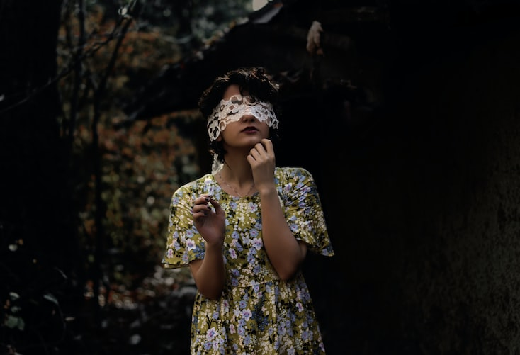 A photo of a woman standing alone in a forest wearing a floral dress with a blindfold over her eyes.