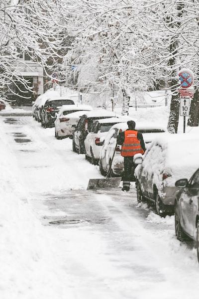 man wearing orange vest holding black snow shovel on snow street near the cars during winter