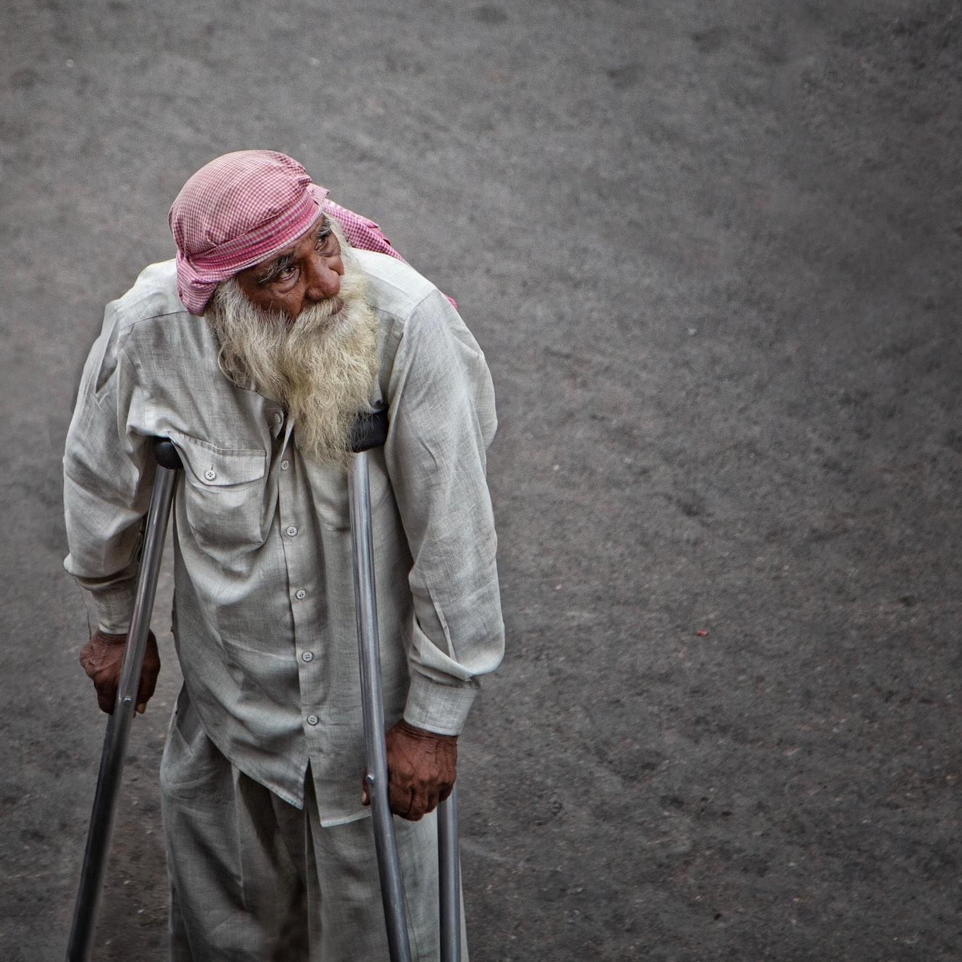 man in dress shirt using axilliary crutches