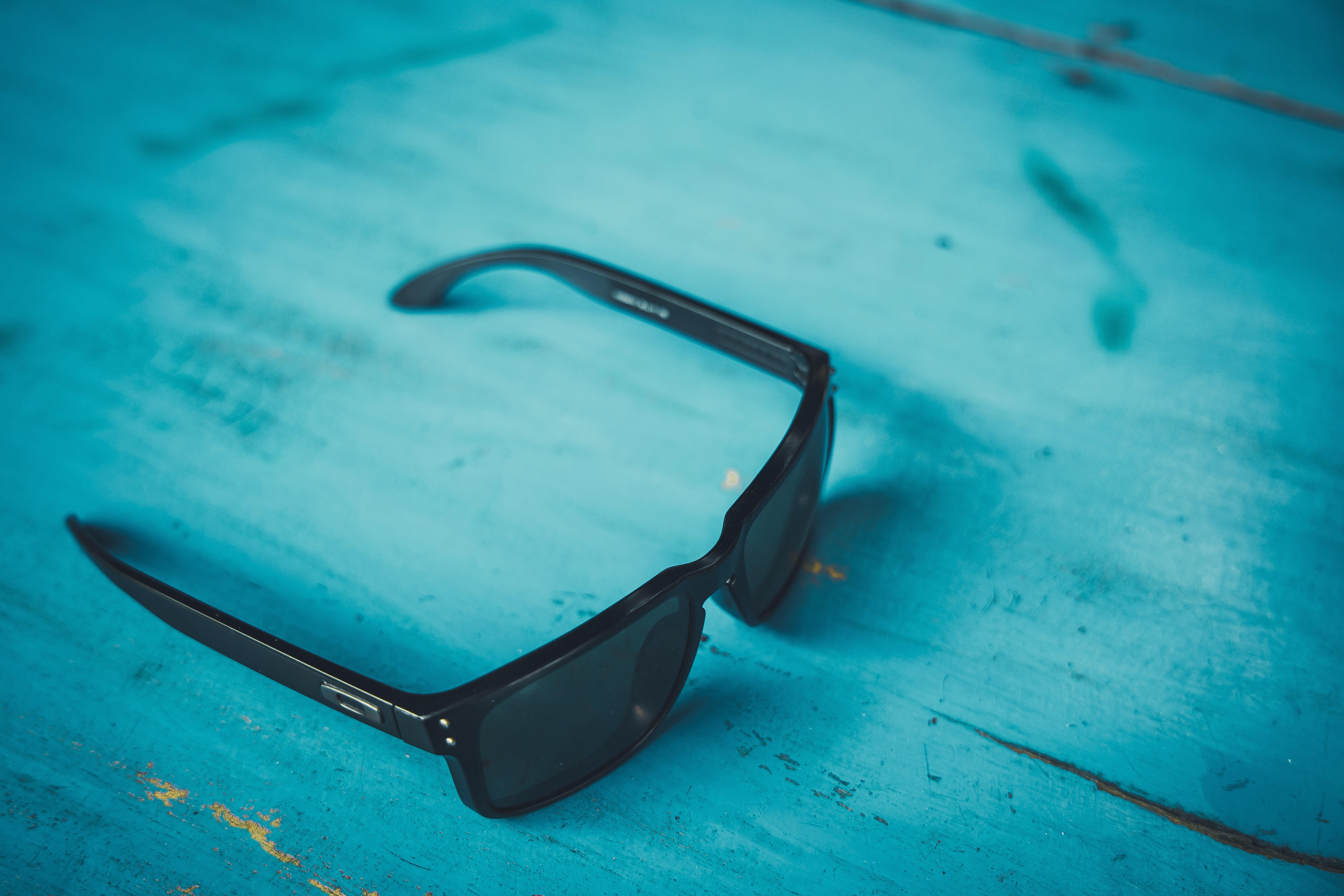 black framed black lens sunglasses on blue surface