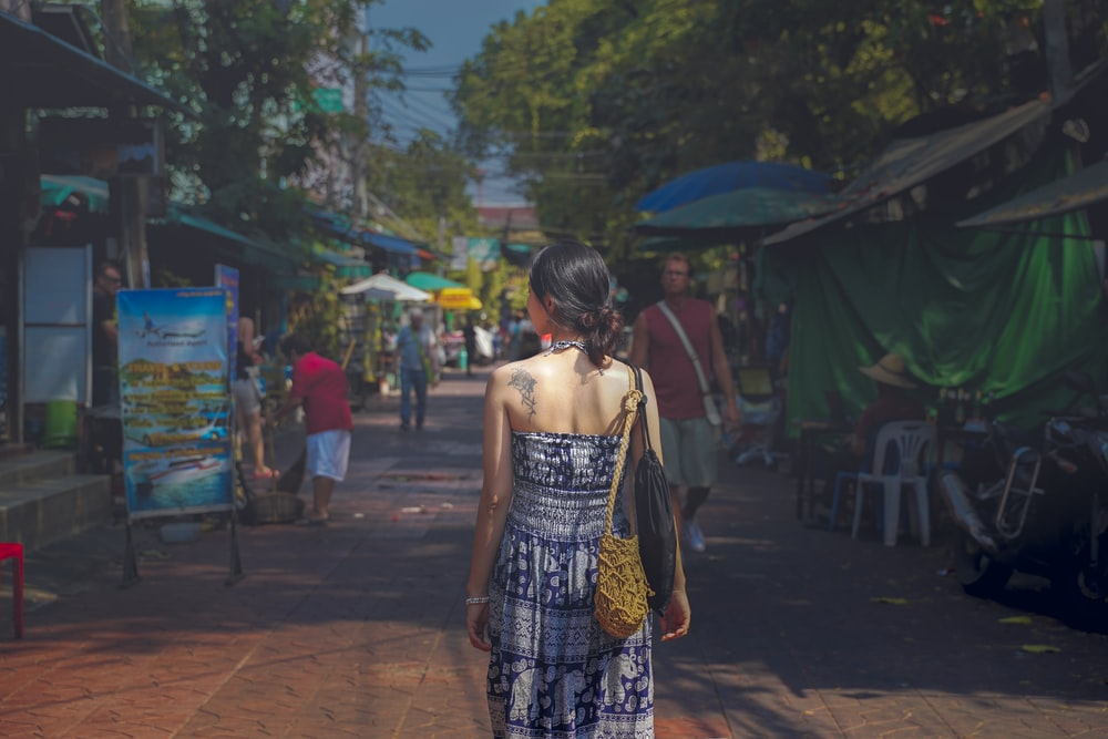 woman wearing halter maxi dress walking on pathway between stores