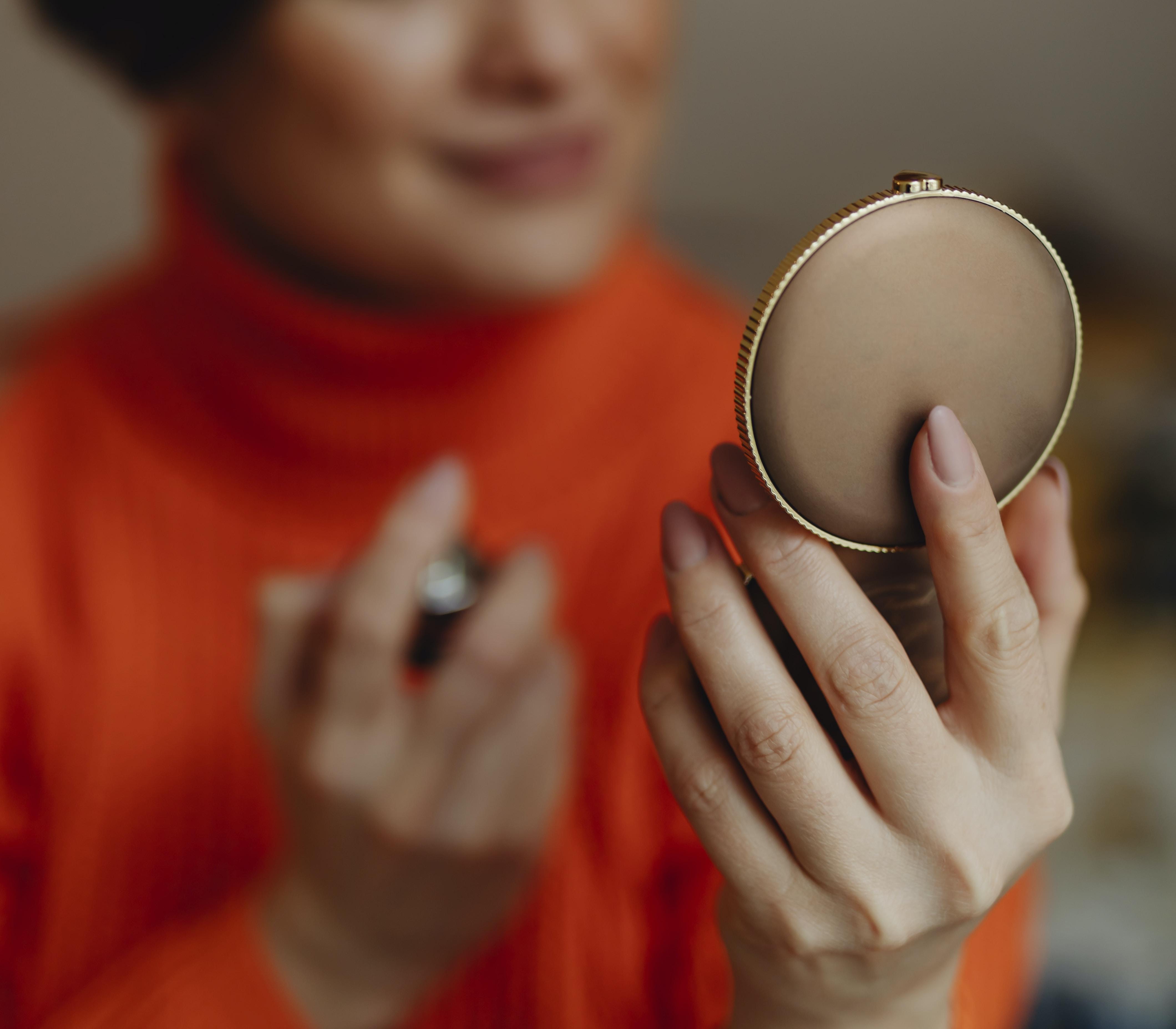 tilt shift focus photography of woman holding handheld mirror