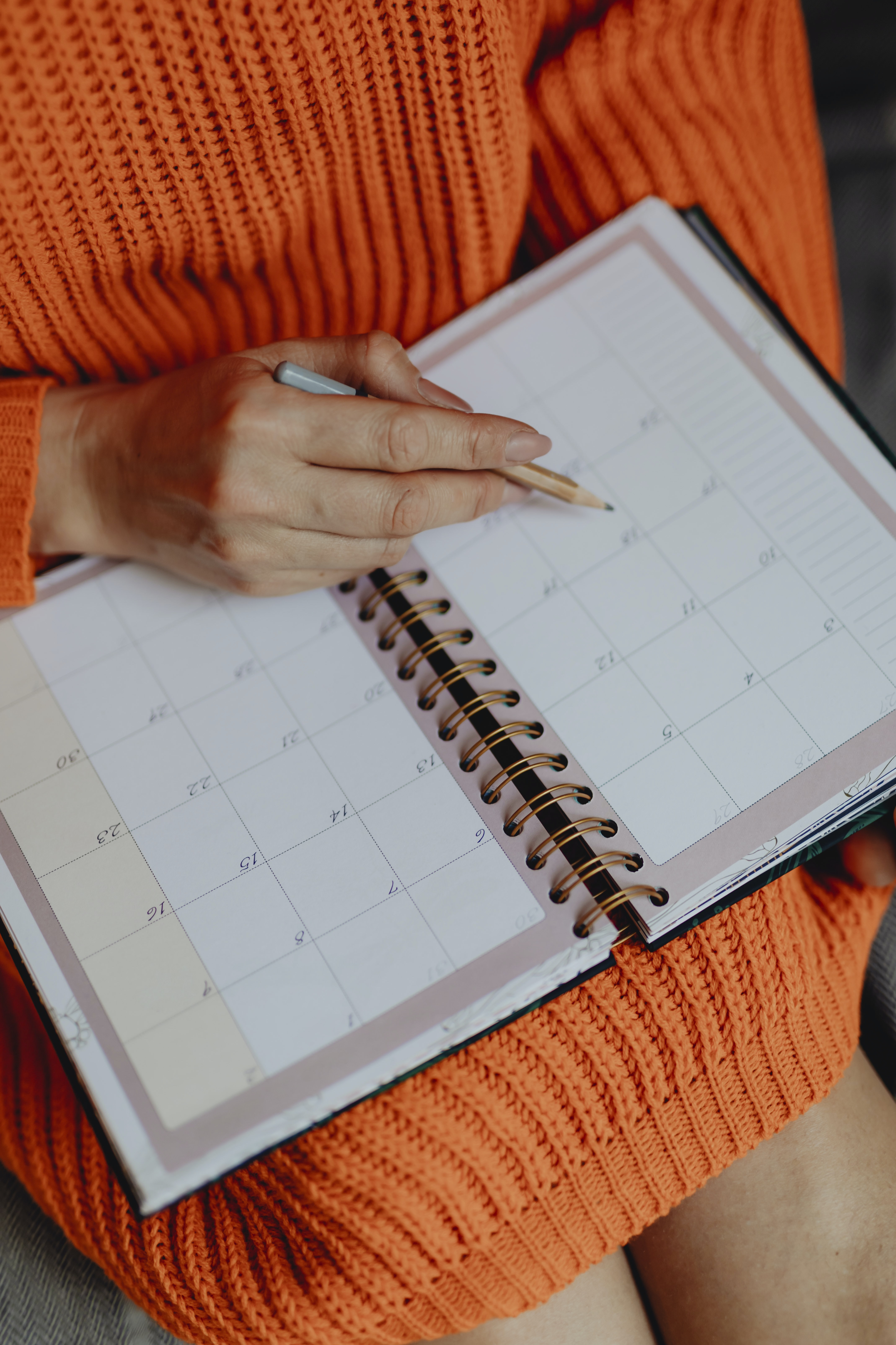 woman in orange knitted dress writing notes on book