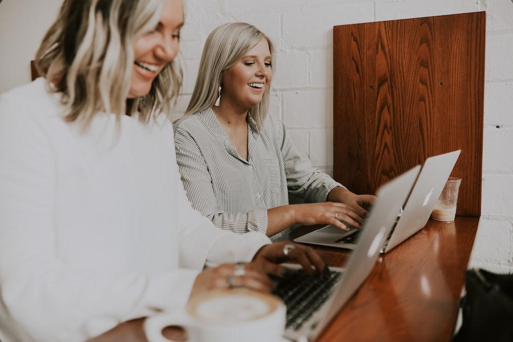 two women using laptops