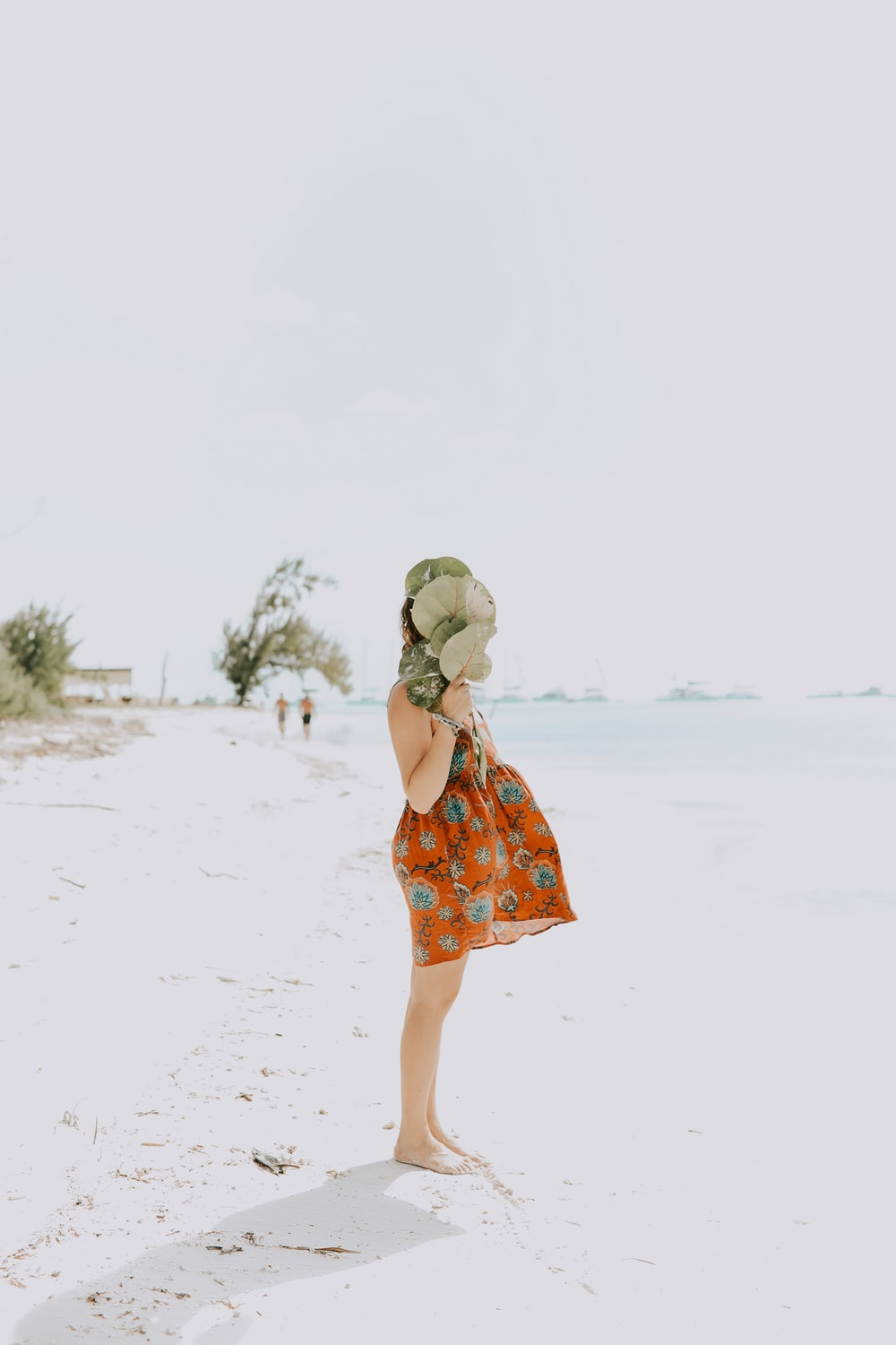 girl wearing orange and green floral dress standing on beige sand during daytime