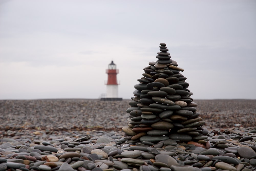 selective focus photography of stocked stones with lighthouse background