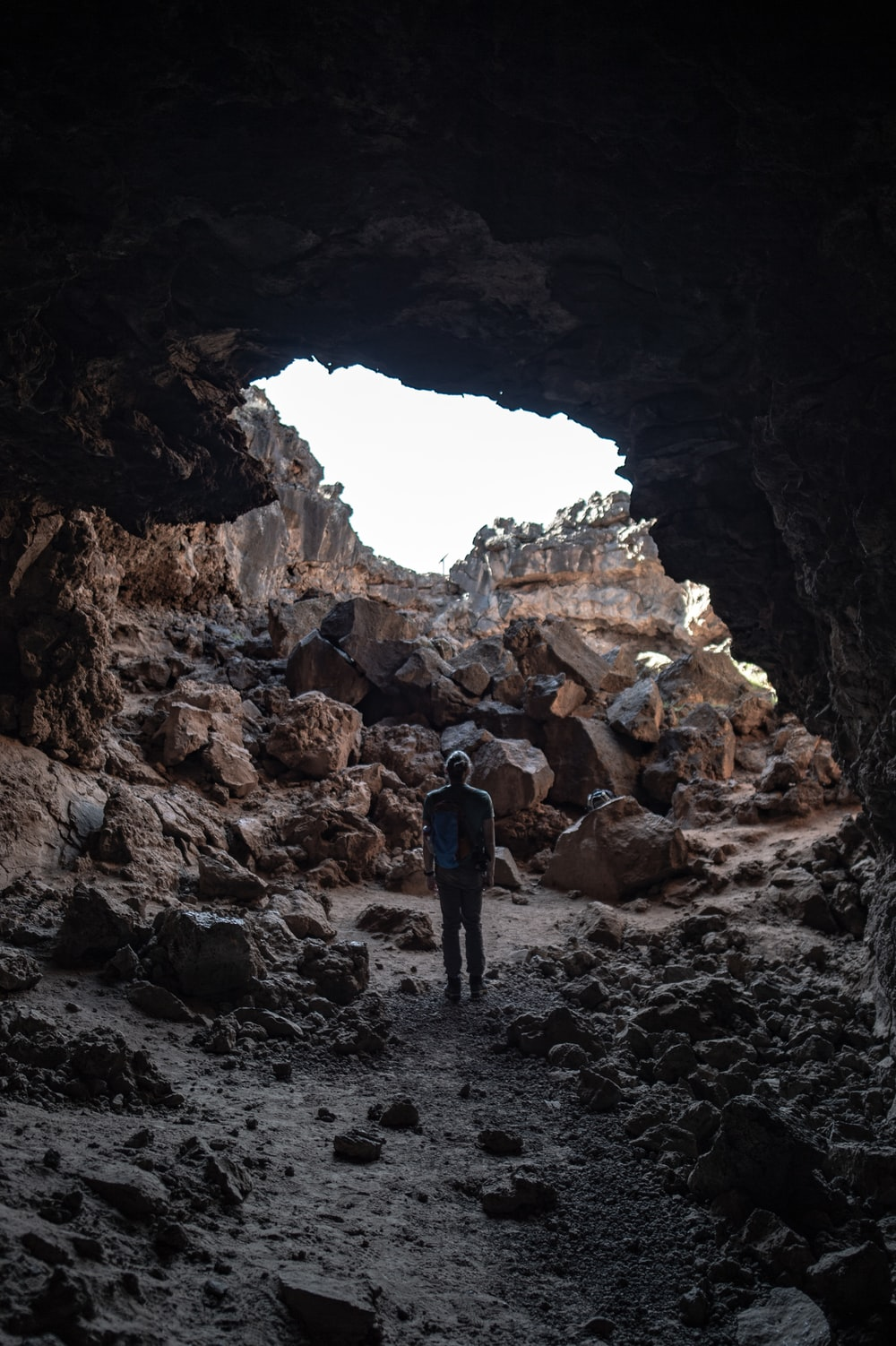 focus photography of man standing on cave
