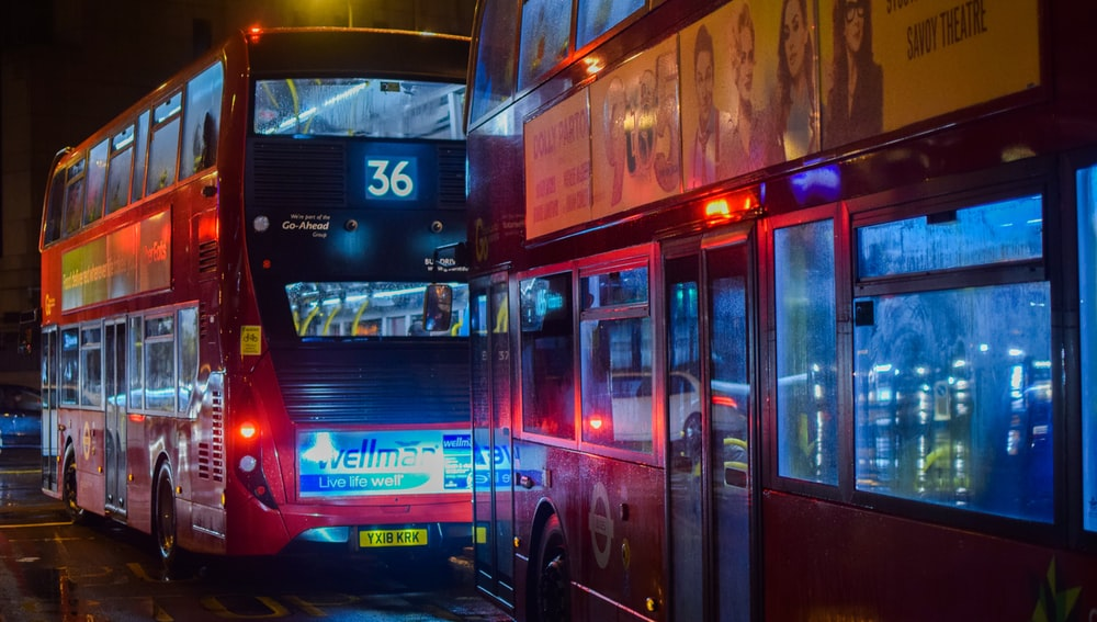 two red buses on road at night