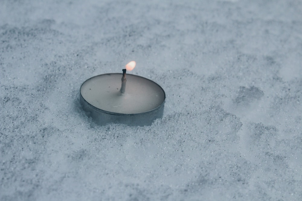 close up photography of tealight candle on snow field