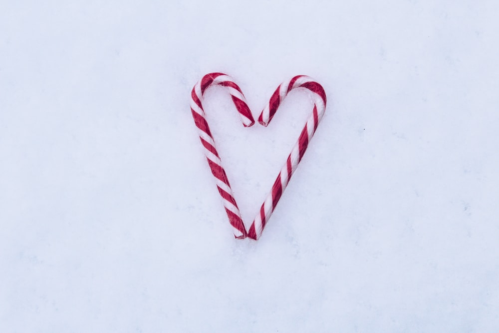 two red-and-white candy canes on white surface