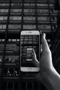 grayscale photography of person holding iPhone taking photo of building