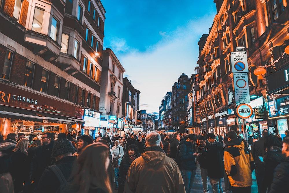 people walking on street between commercial buildings