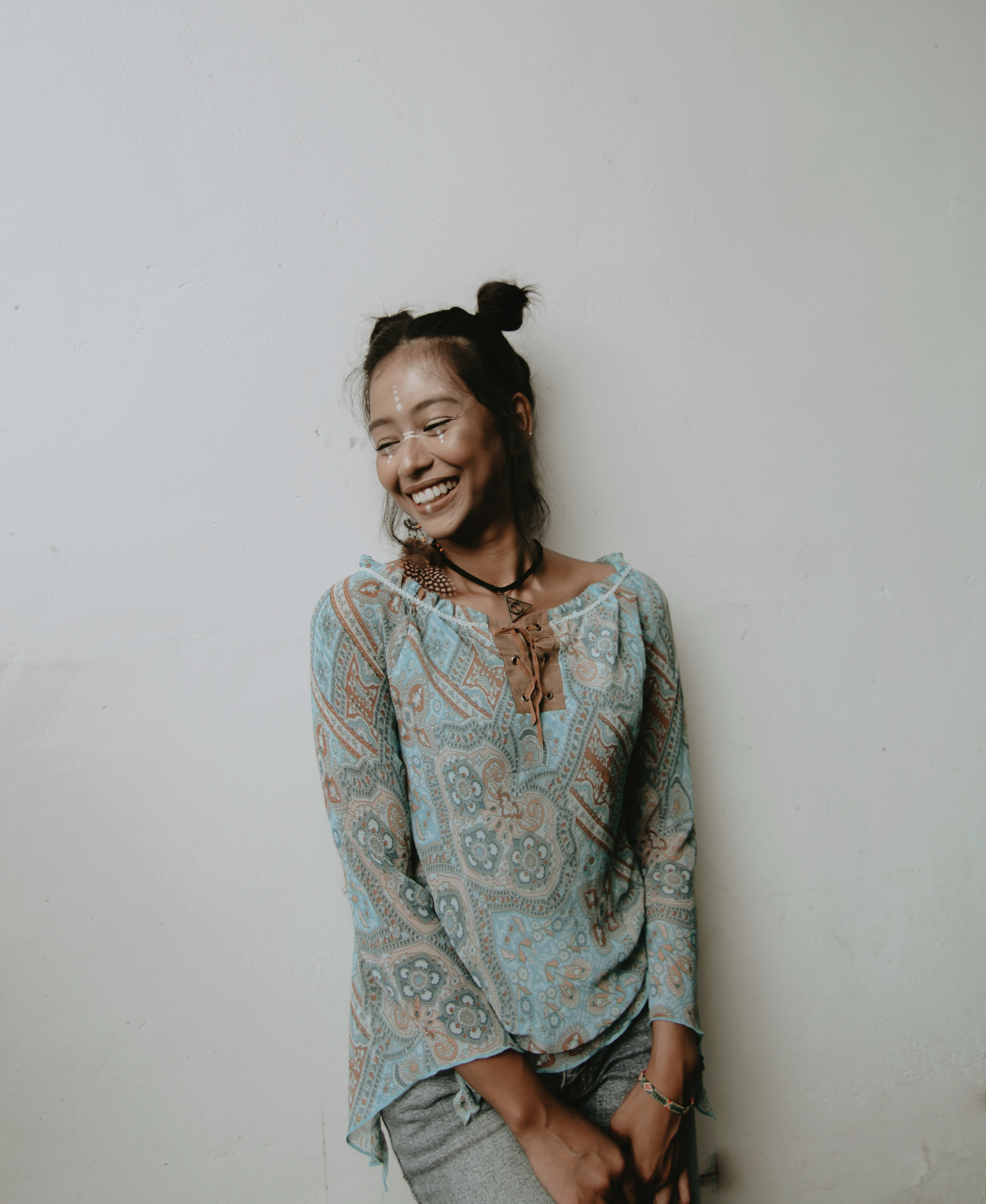 smiling woman wearing blue blouse leaning on wall