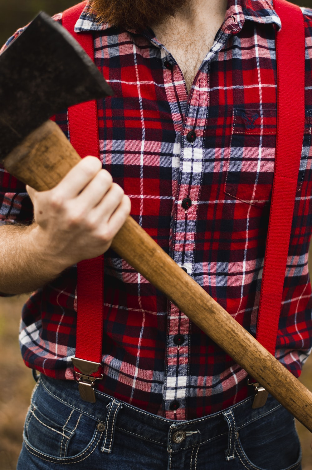 person carrying brown handle axe