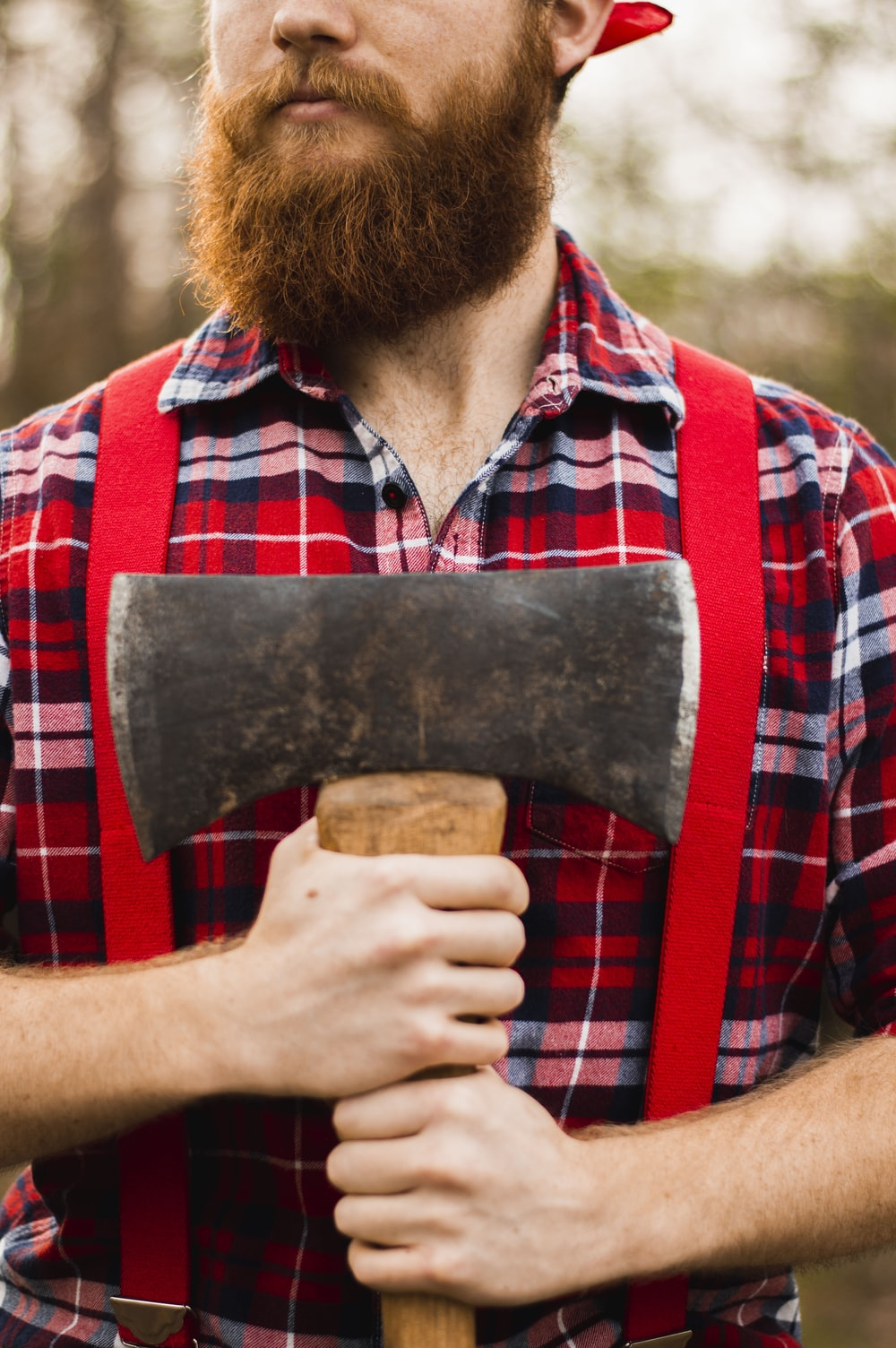 man holding red, blue, and white plaid shirt holding ax