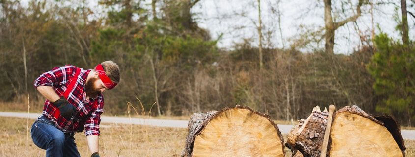 person using chainsaw in front of tree log