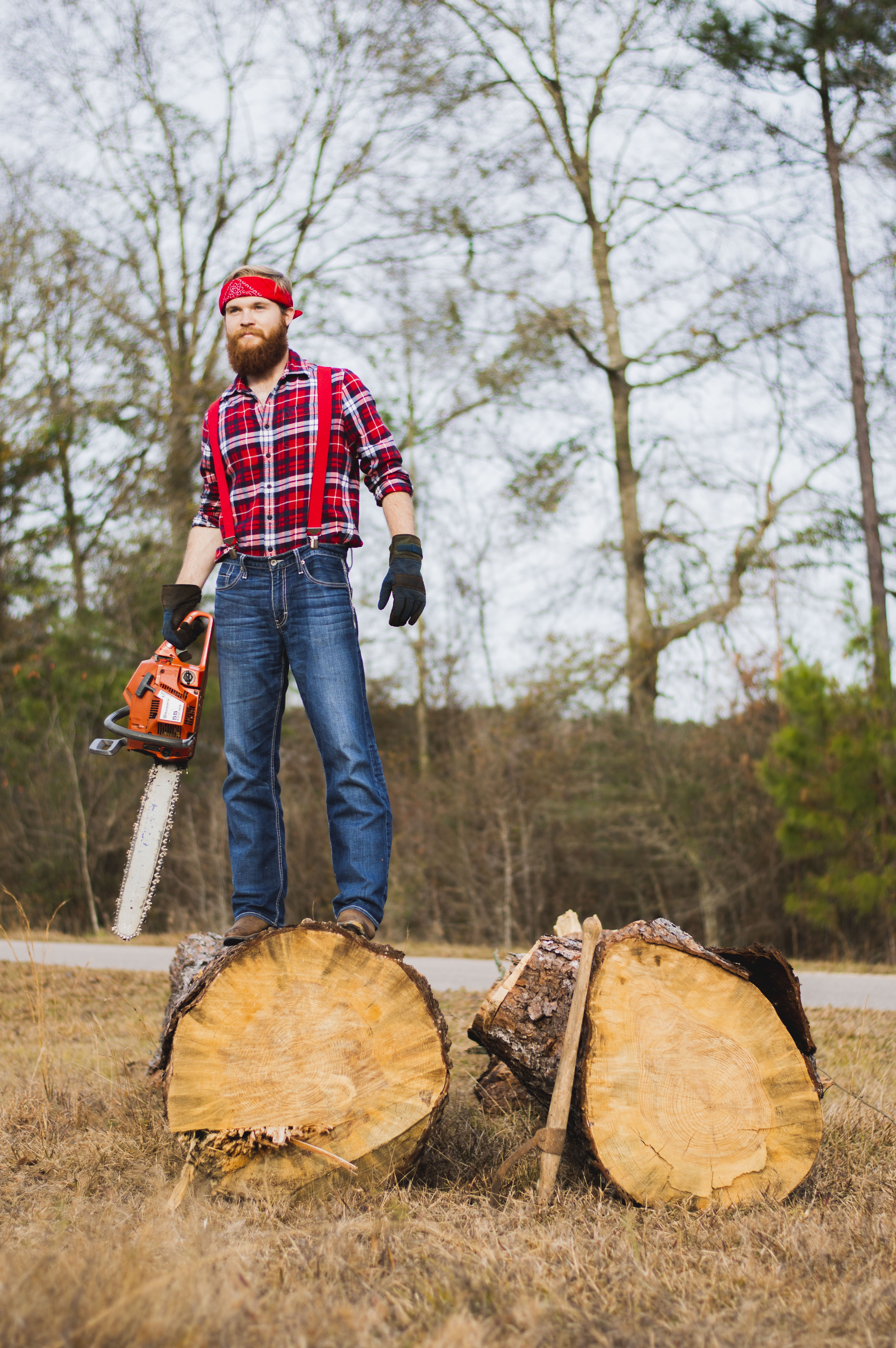 man holding chainsaw and standing on wood log