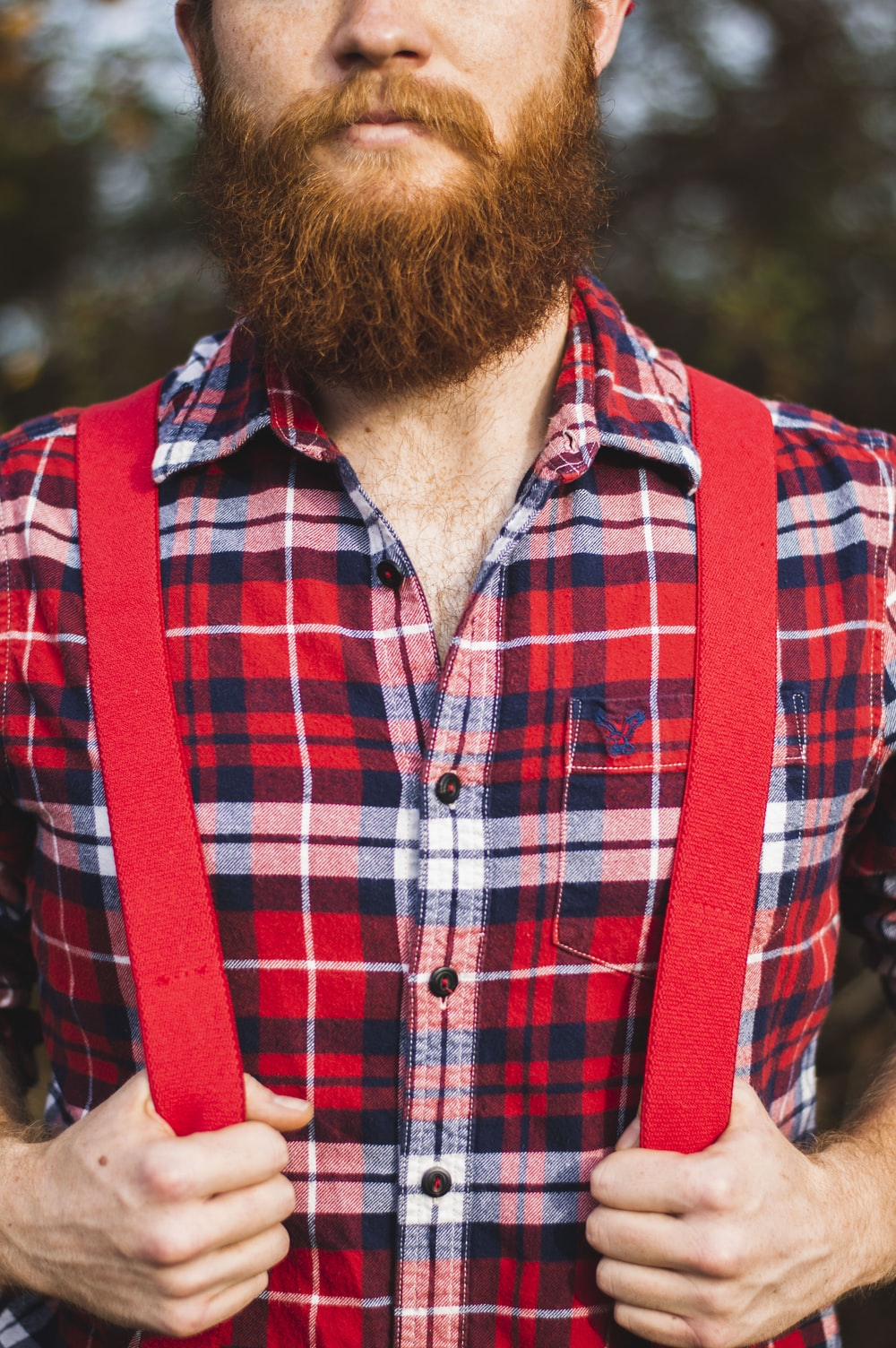 man in red, blue, and white plaid dress shirt with red suspender during daytime