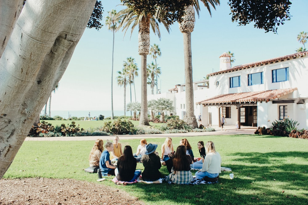 people sitting on ground while forming round during daytime