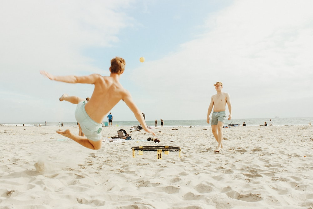 two men playing on seashore