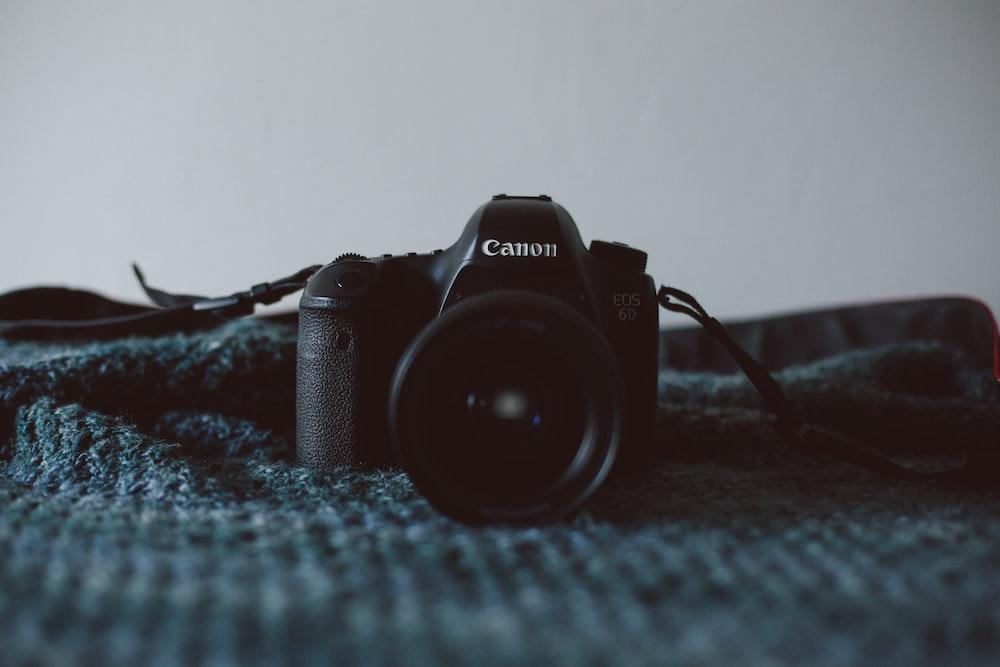 black Canon DSLR camera on black textile