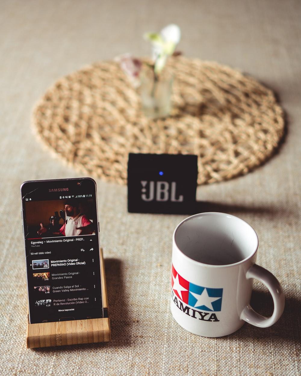 black Samsung smartphone playing video beside white ceramic mug and black JBL Go speaker