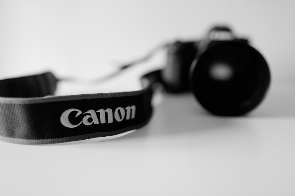black Canon DSLR camera in grayscale photo