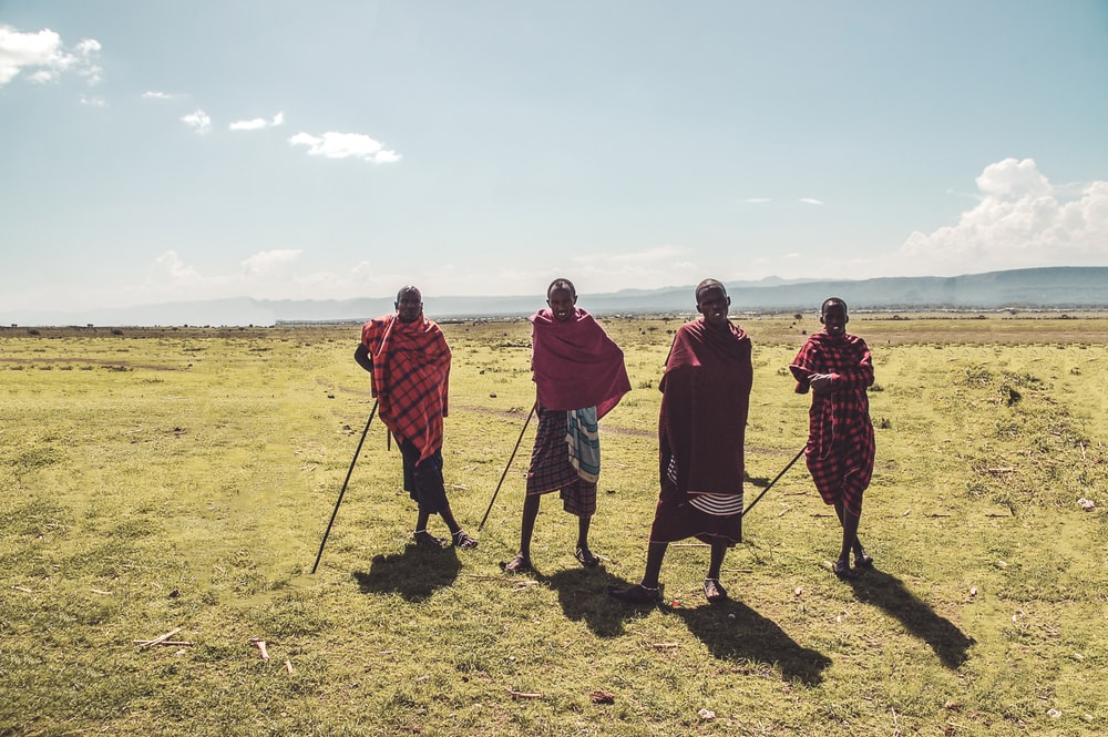 four man standing on green grass during daytime