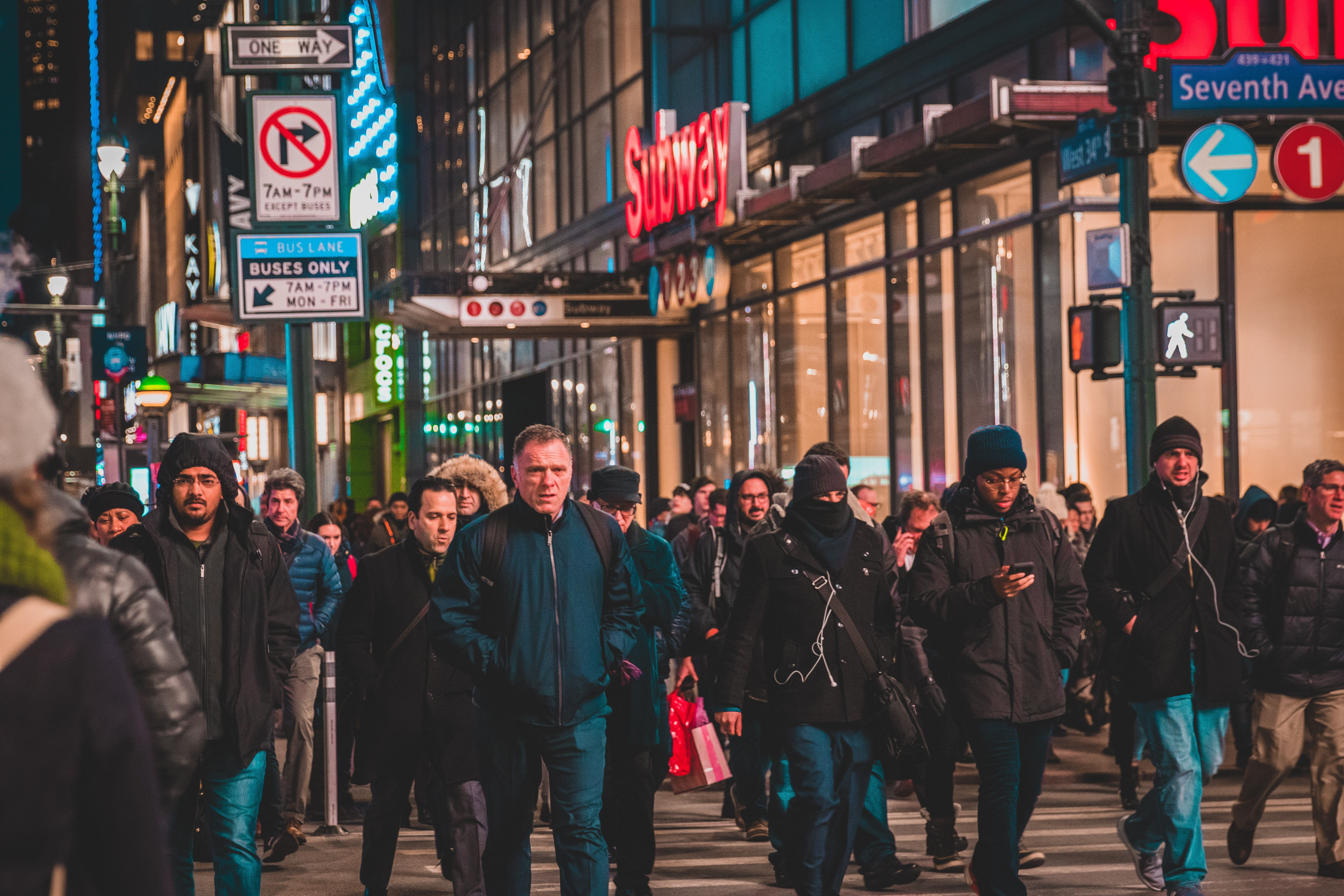 crowd of people walking on street at night time