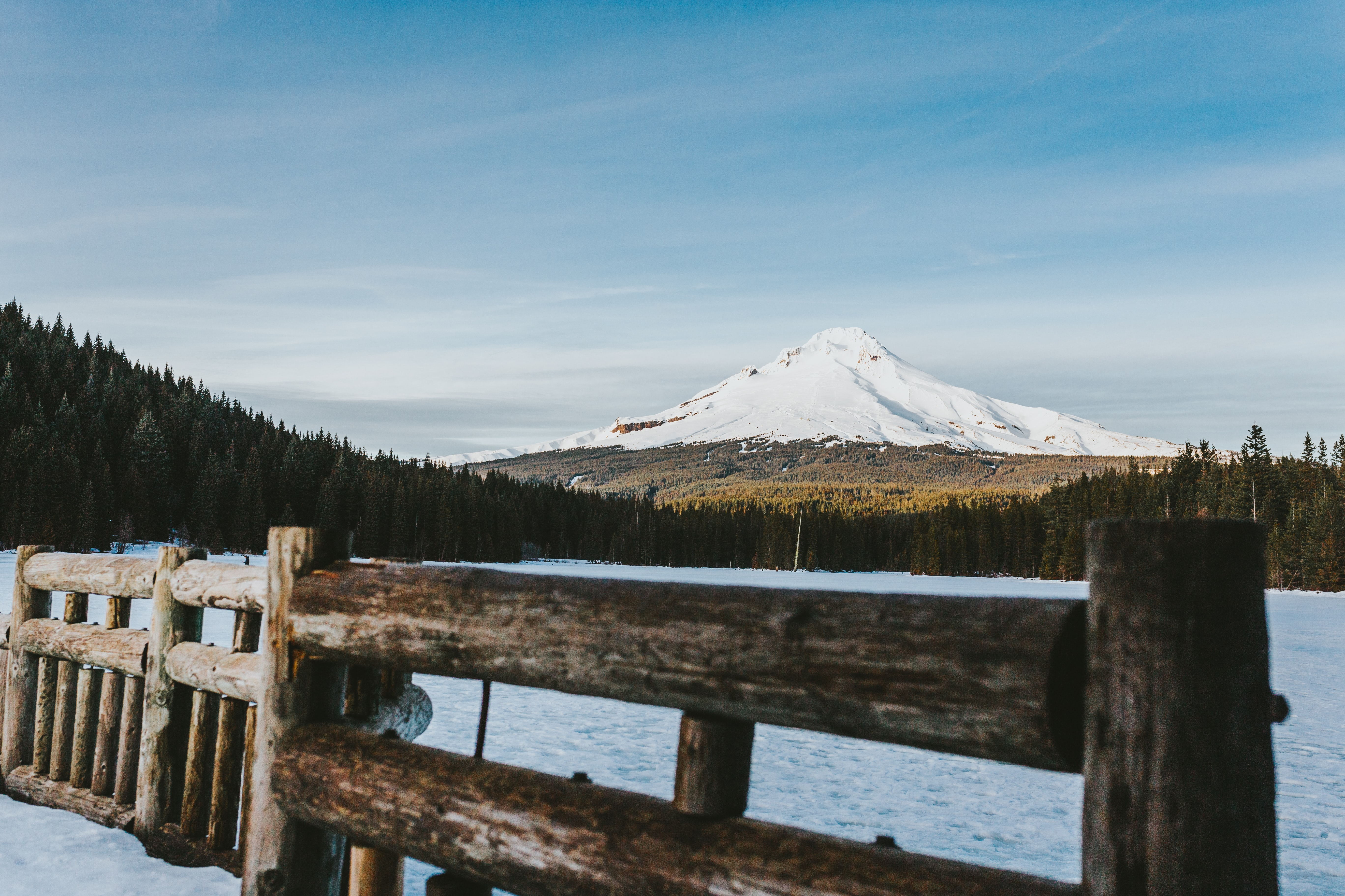 brown wooden fence near lake with view of snow capped mountain