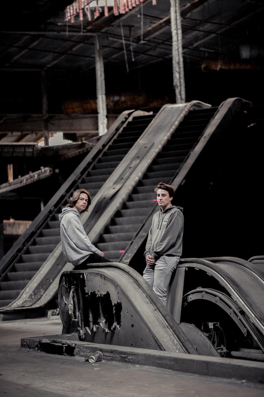 two men sitting on railing inside building photo - Free ...