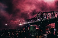 concrete bridge at night time with red smoke