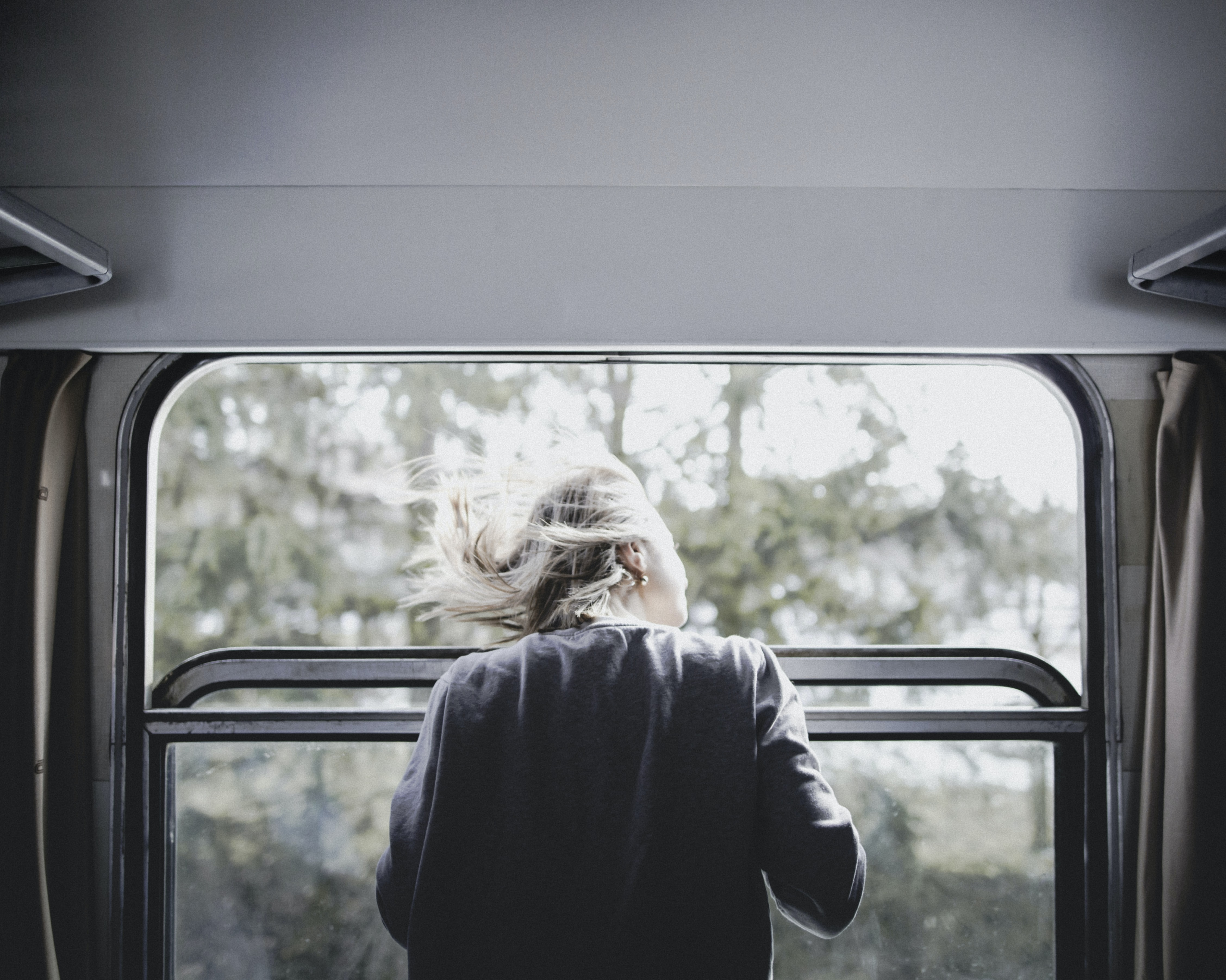 woman wearing black jacket leaning on train window looking at something