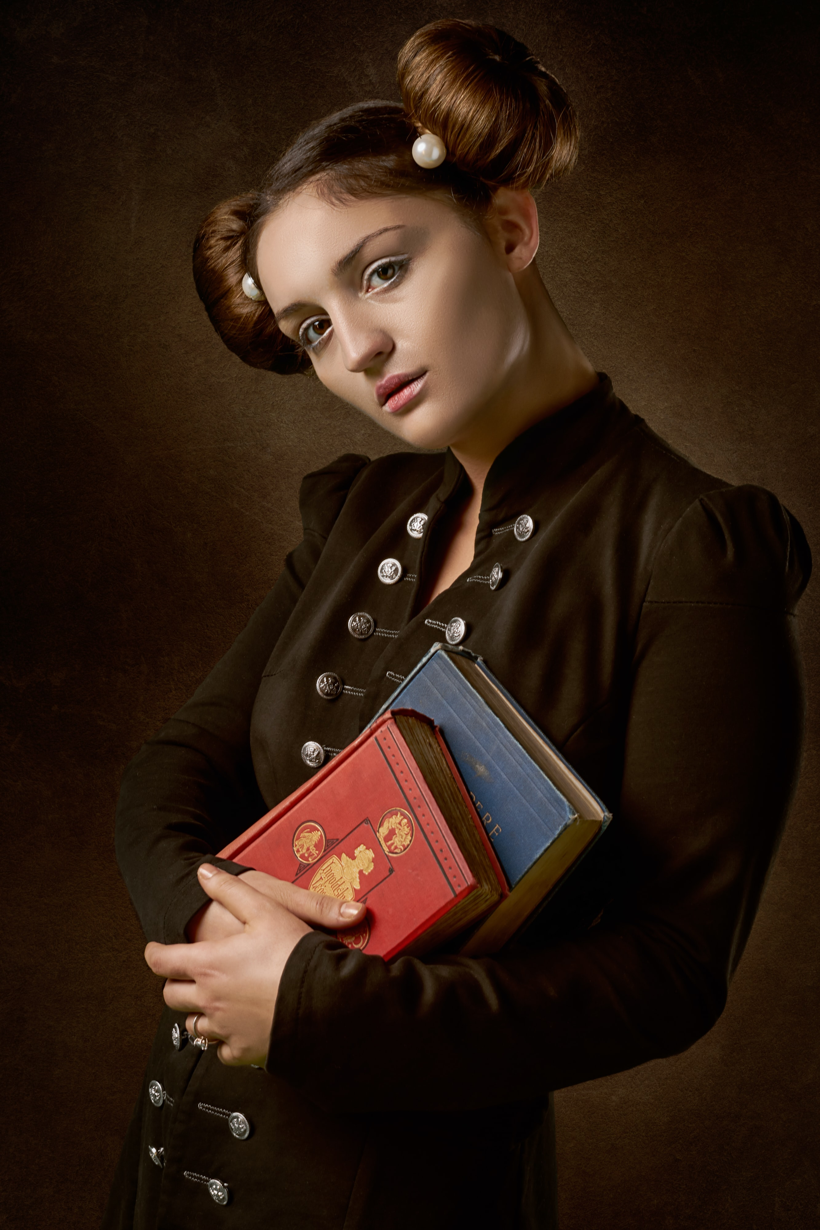 woman holding two red and blue labeled books