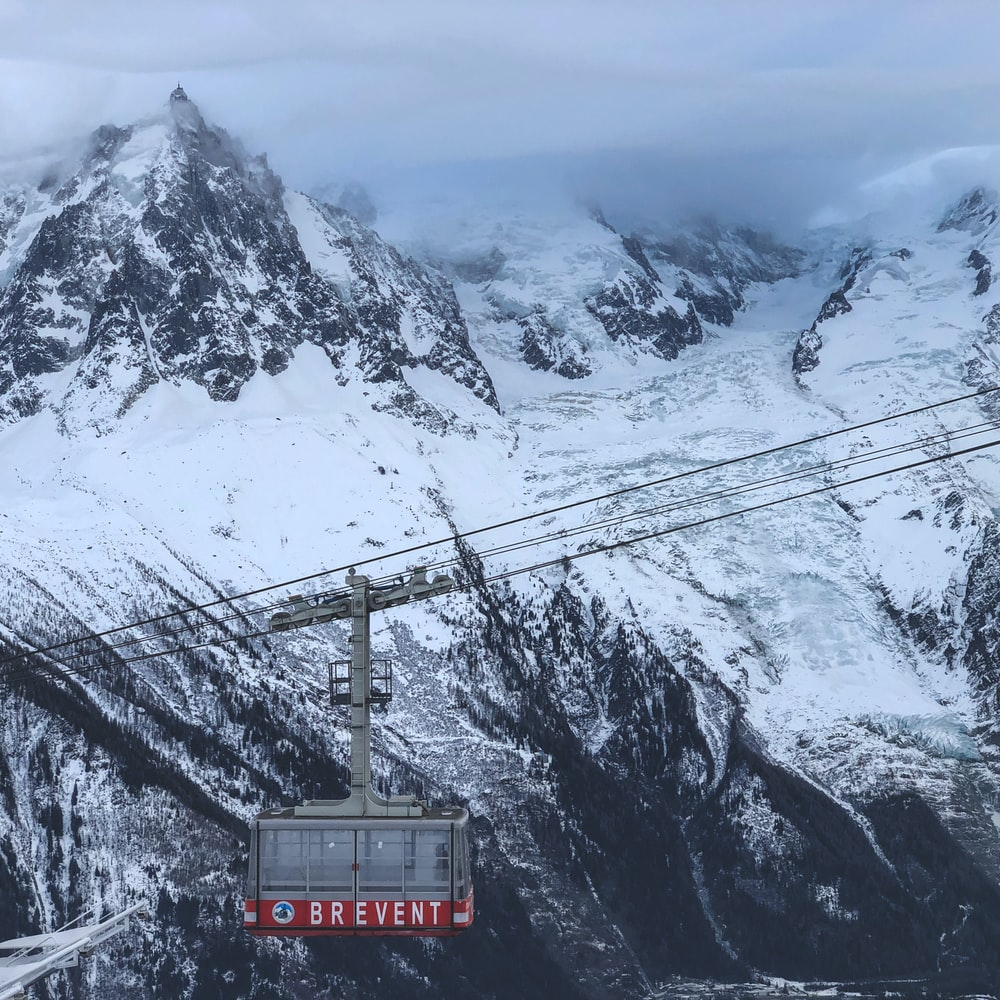gray and red cable car near mountain covered with snow
