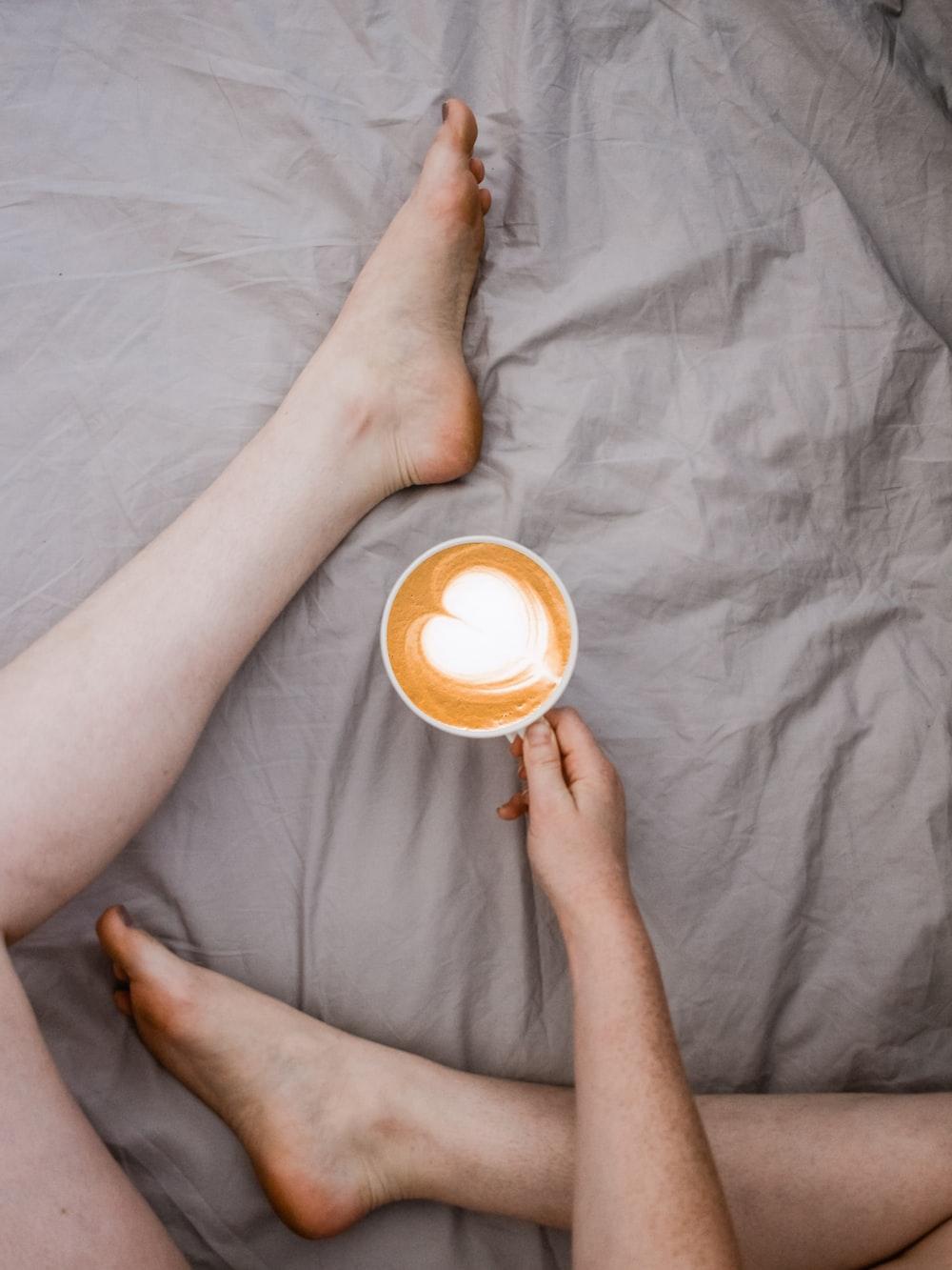 person holding white mug sitting on bed