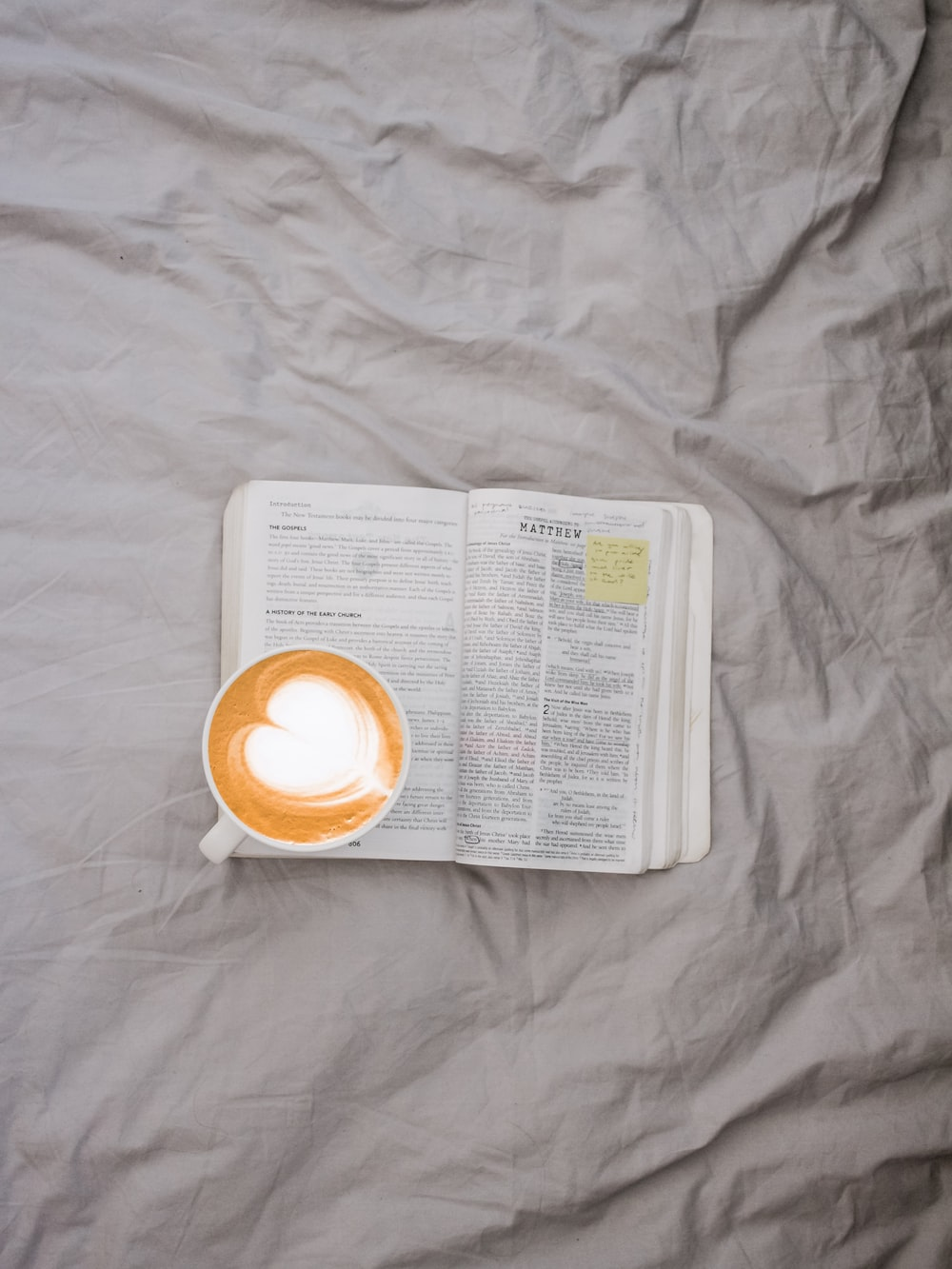white mug filled with coffee on top of book