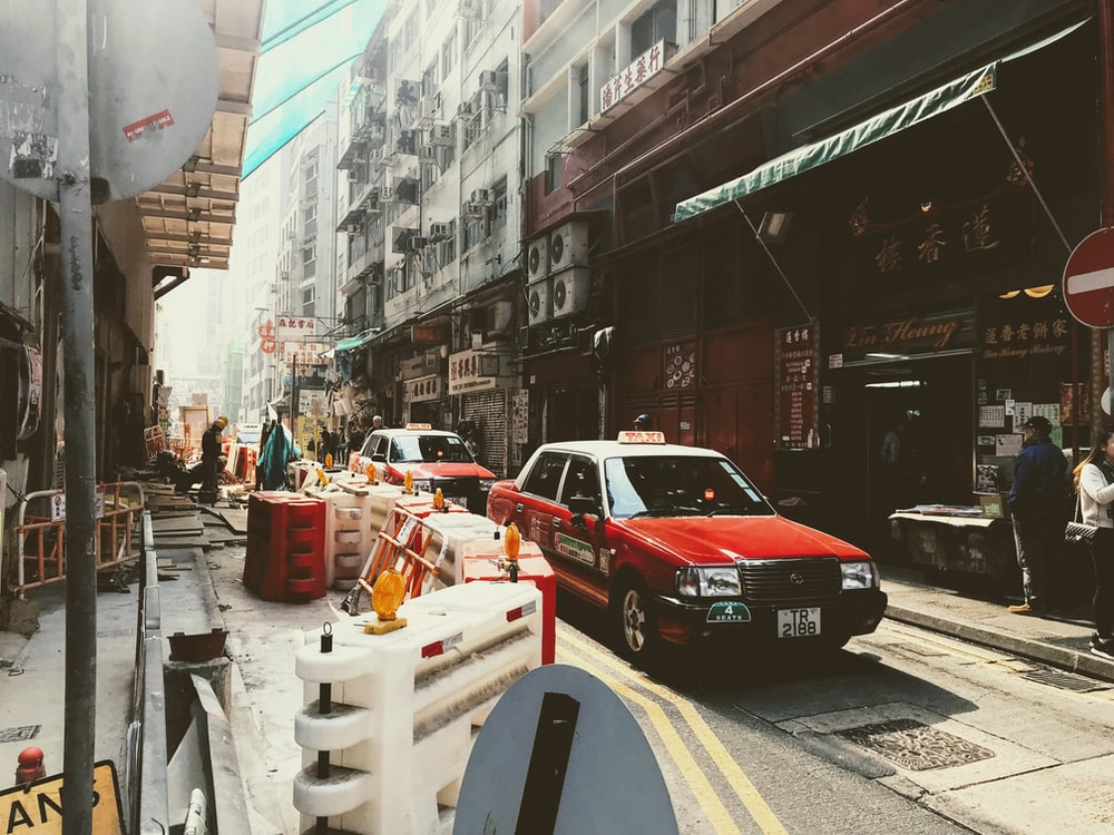 red sedan driving on concrete road between buildings