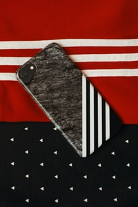 black iPhone on red and white textile