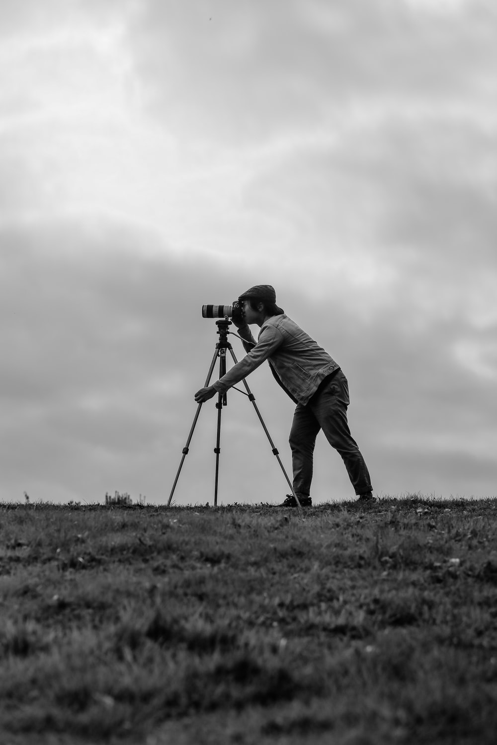 grayscale photo of man standing beside camera