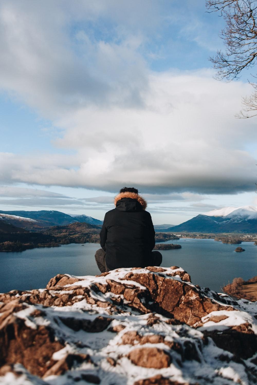 man sitting on mountain peak