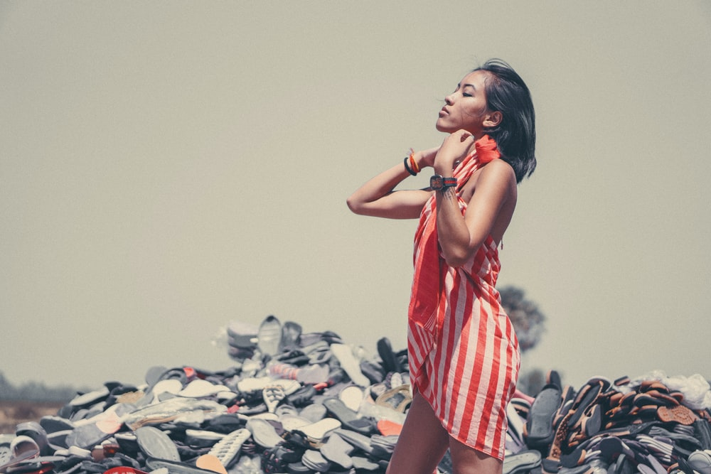 standing woman in front of pile of shoes