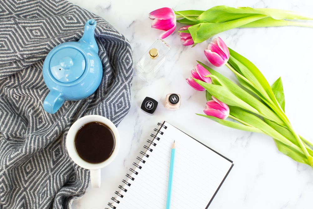 cup of coffee beside tulips and spiral notebook