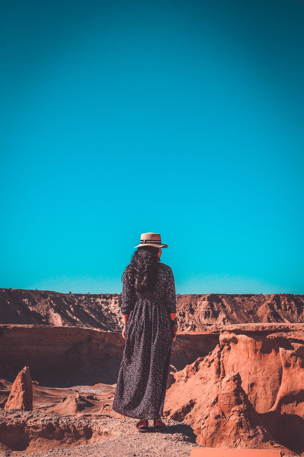 woman in dress and hat stands at the valley