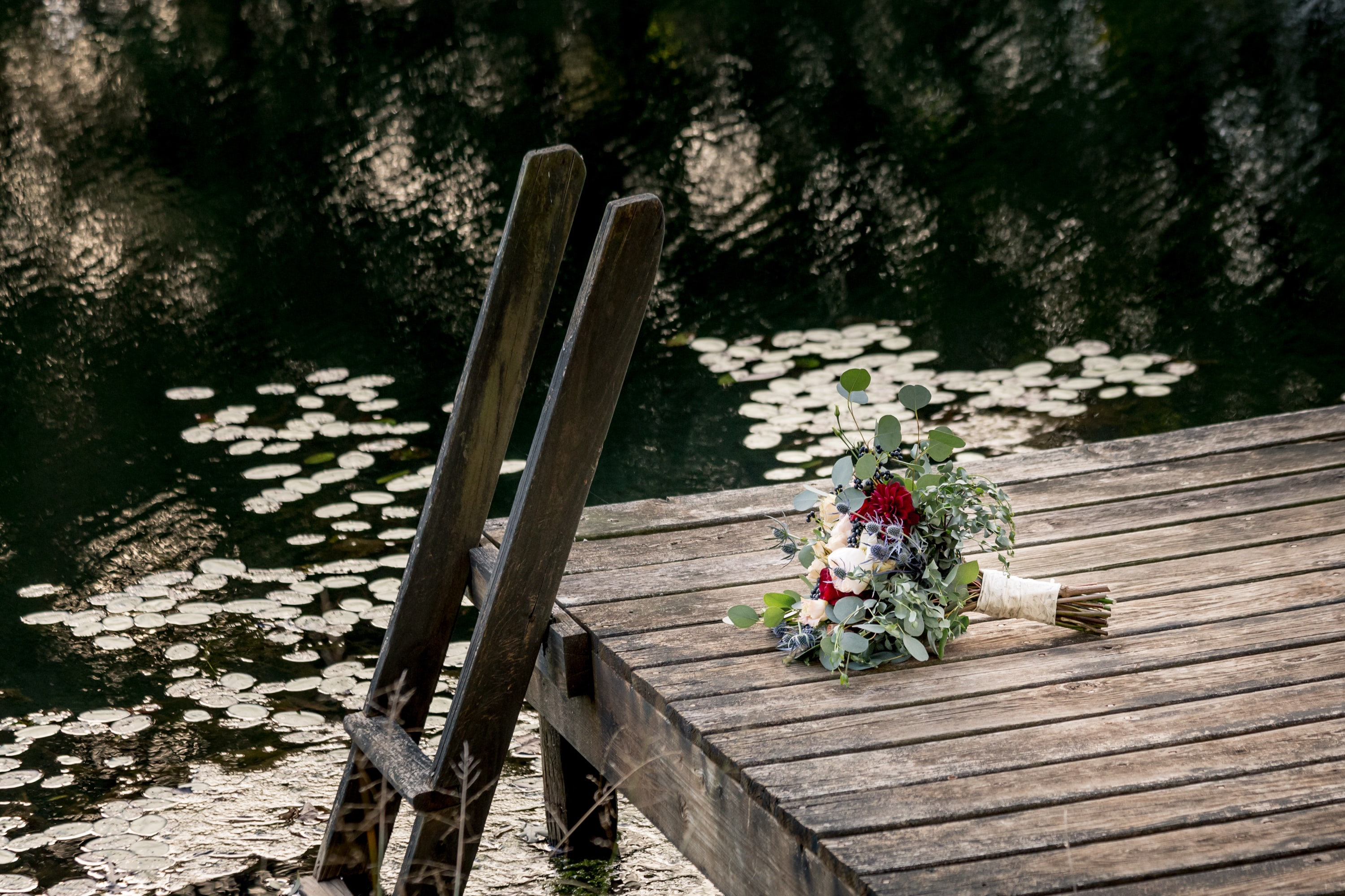 wedding bouquet on dock near ladder by the lake