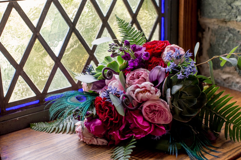 multicolored bouquet beside window